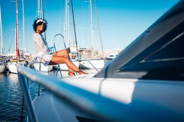 Vrolijke toerist gaat zitten en lacht terwijl hij geniet van de zomervakantie op een boot