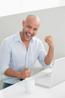 Vrolijke toevallige mens die laptop thuis met behulp van