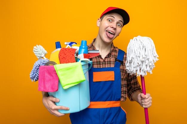 Vrolijke tong die jonge schoonmaakster in uniform draagt en pet met emmer schoonmaakgereedschap met dweil
