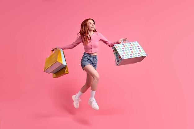 Vrolijke trendy stijlvolle zorgeloze vrouw die zich verheugt met verkoop winkeltijd geïsoleerd op roze studio achterkant...