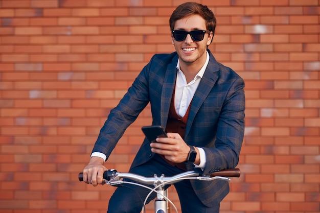 Vrolijke trendy zakenman met telefoon op de fiets