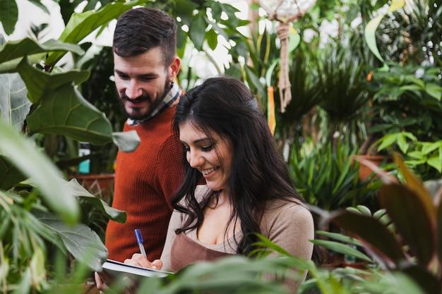 Vrolijke tuinlieden die aantekeningen maken