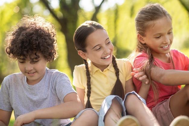 Vrolijke twee meisjes en jongen in zomerpark