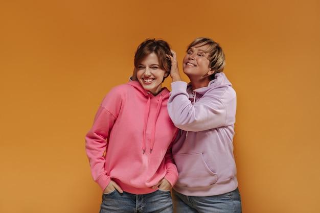 Vrolijke twee vrouwen met kort haar in brede stijlvolle hoodies en coole spijkerbroek glimlachend en plezier op oranje geïsoleerde achtergrond.