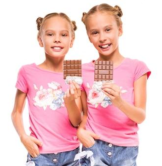 Vrolijke tweelingmeisjes eten een chocolade.