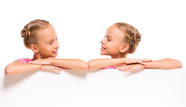 Vrolijke tweelingmeisjes met een wit bord.