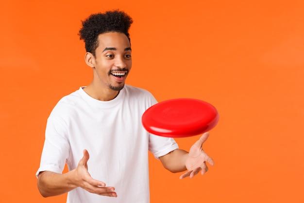 Vrolijke uitgaande knappe afro-amerikaanse jongeman met afro kapsel, snor, glimlachend geamuseerd rode frisbee vangen als buiten spelen, zoals actieve games, oranje achtergrond