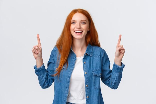 Vrolijke uitgaande verleidelijke roodharige vrouw, lang rood kapsel, toppromotie, wijzende vingers omhoog en lachend, lachend geamuseerd, positieve beoordeling achterlaten