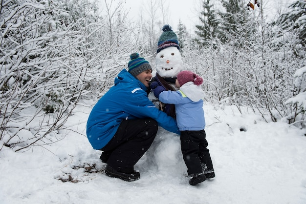 Vrolijke vader en dochter die sneeuwman maken