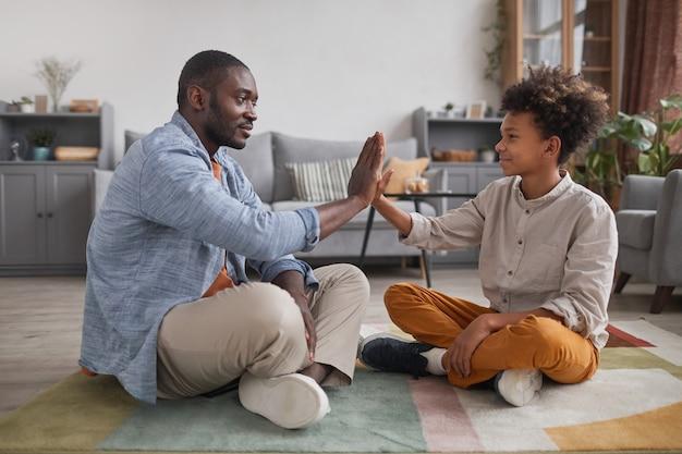 Vrolijke vader en zijn tienerzoon brengen tijd thuis door, zittend op de vloer in de woonkamer en spelen een klappend spel