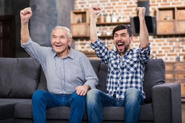Vrolijke vader en zijn zoon thuis rusten tijdens het kijken naar voetbal