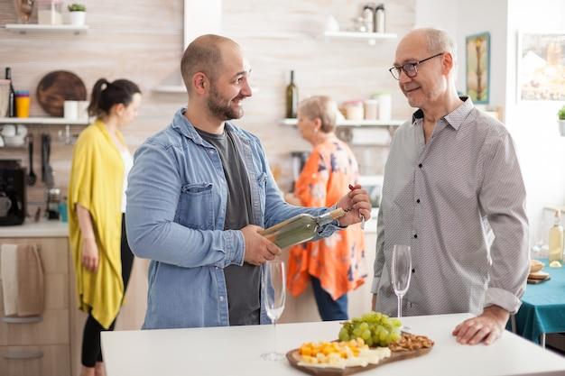 Vrolijke vader en zoon praten in de keuken terwijl de rest van het gezin bezig is met het bereiden van maaltijden. man met fles wijn.