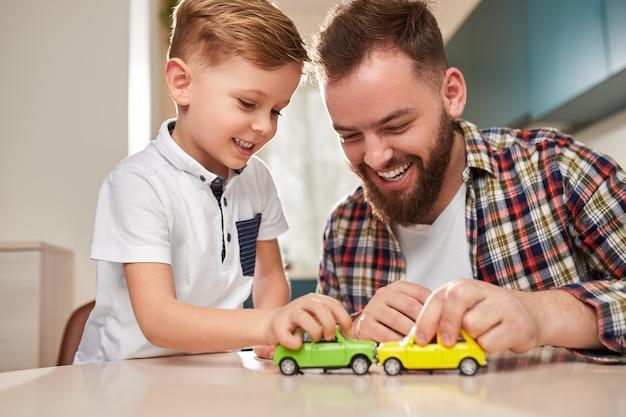Vrolijke vader en zoon spelen met auto's