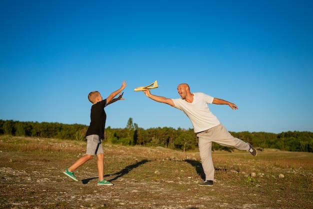 Vrolijke vader en zoon spelen per vliegtuig in de natuur