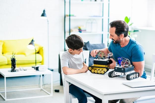 Vrolijke vader en zoon zitten aan tafel terwijl ze hun robotapparaten bouwen