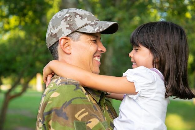 Vrolijke vader in camouflage uniform dochtertje in armen houden, meisje buitenshuis knuffelen na terugkeer van militaire missie reis. close-up shot. familiereünie of het concept van thuiskomst