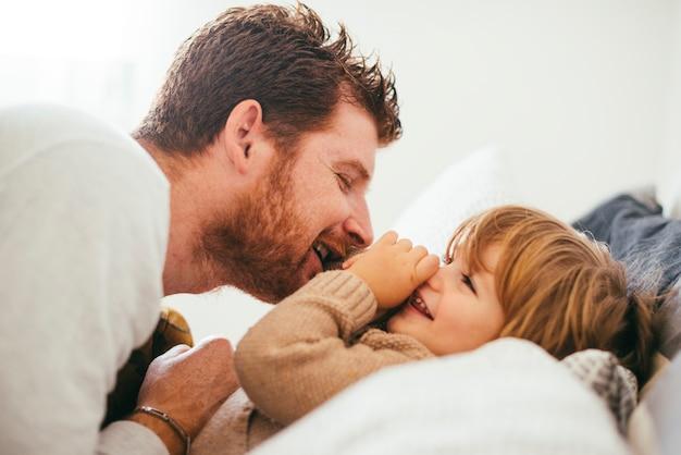 Vrolijke vader spelen met peuter