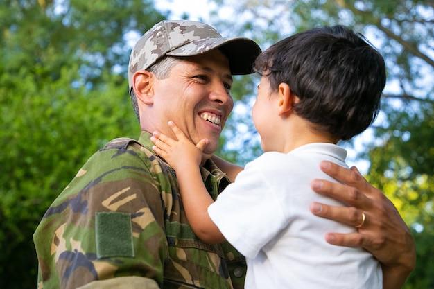 Vrolijke vader zoontje in armen houden, jongen buiten knuffelen na terugkeer van militaire missie reis. lage hoek. familiereünie of het concept van thuiskomst