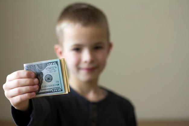 Vrolijke vage jongen die amerikaans dollarsgeld toont.