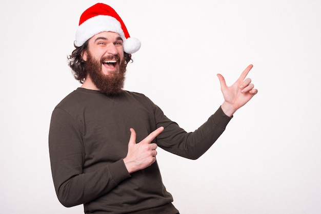 Vrolijke verbaasde bebaarde hipster man met kerstman hoed en wijzend op copyspace