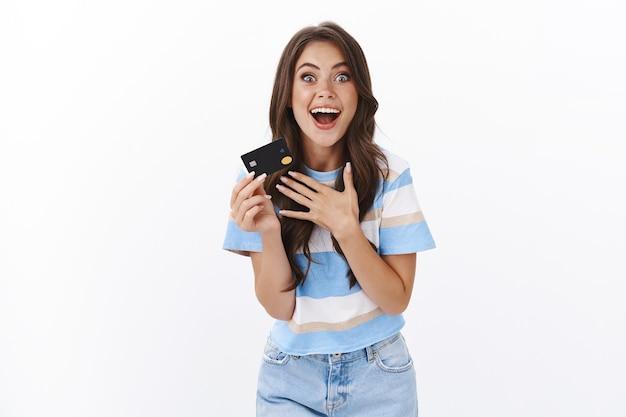 Vrolijke verbaasde knappe vrouw met creditcard, gebaren enthousiast onder de indruk van geweldige bankaanbieding, bidden voor cashback en coole kortingen, betalen voor online winkelen