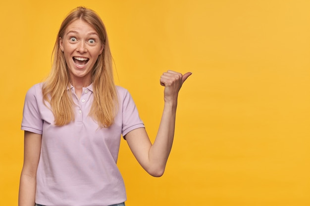 Vrolijke verbaasde vrouw met sproeten in lavendelkleurige t-shirt voelt zich opgewonden en wijst naar de zijkant op copyspace op geel