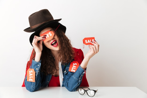 Vrolijke verkoop winkelende vrouw die verkooptekens draagt