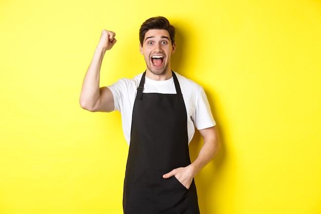 Vrolijke verkoper die vuistpomp maakt, zich verheugt en triomfeert, staande in zwarte schort tegen gele achtergrond.