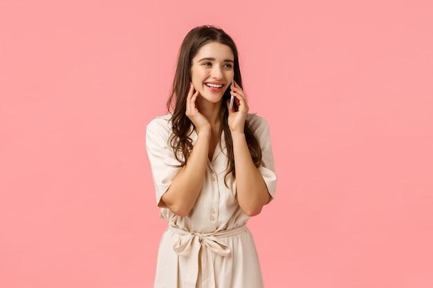 Vrolijke verleidelijke en zorgeloze gelukkige vrouw in jurk, lachend praten over de telefoon, beste vriend bellen en romantische date bespreken, smartphone bij oor houden, zijwaarts kijken, roze muur