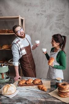 Vrolijke verliefde paar bakkers koffie drinken. opzij kijken.