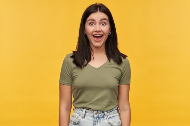 Vrolijke verraste jonge vrouw met donker haar en geopende mond in vrijetijdskleding kijkt verbaasd over gele muur