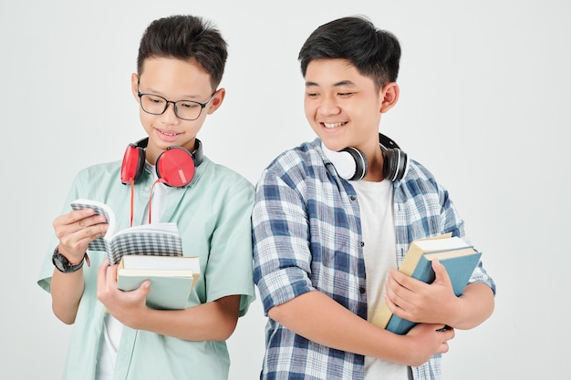Vrolijke vietnamese schooljongen die zich met studentenboeken bevindt die zij voor het nieuwe schooljaar hebben ontvangen
