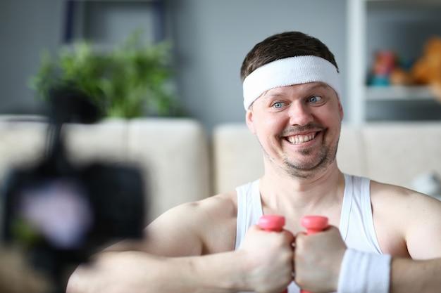 Vrolijke vlogger met halters in handenportret. glimlachende sportman opname fitness oefening op digitale camera voor sport vlog
