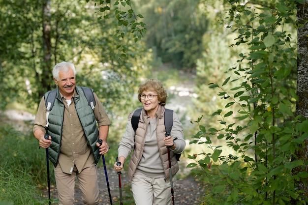 Vrolijke volwassen actieve paar genieten van wandelen in het bos of park tijdens het verplaatsen tussen struiken