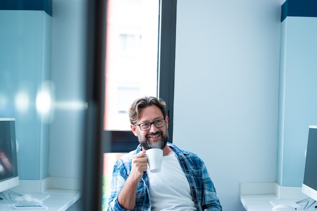 Vrolijke volwassen bebaarde man zit op kantoor glimlach en geniet van een pauze van online werk - mensen en baan levensstijl - blauwe kleuren - knappe volwassen man met bril en koffie - moderne levensstijl