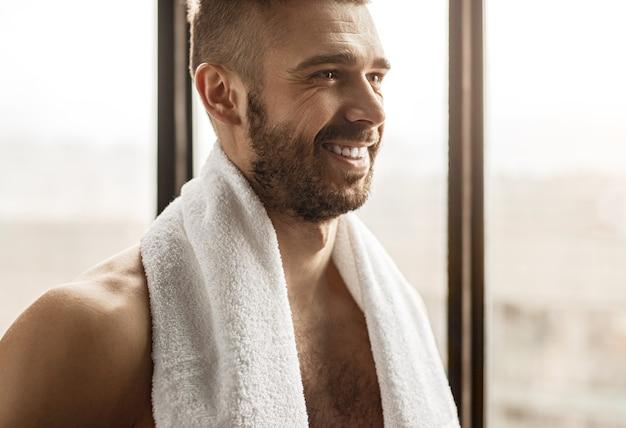 Vrolijke volwassen bebaarde shirtless sportman met handdoek op nek glimlachen terwijl het hebben van pauze tijdens de training in de sportschool