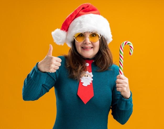 Vrolijke volwassen blanke vrouw in zonnebril met kerstmuts en santa stropdas houdt snoepgoed en duimen omhoog geïsoleerd op oranje muur met kopie ruimte