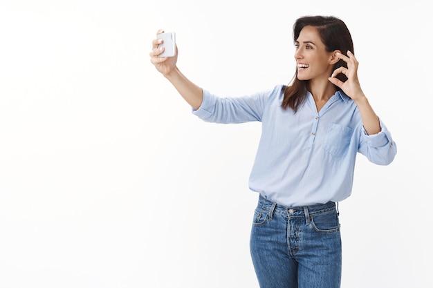 Vrolijke volwassen charmante vrouw met tatoeages draagt blauwe blouse, praat man online, houd smartphone-show oké, goedkeuringsbord mobiele telefoon aan de voorkant, glimlachen, outfit uitchecken via videogesprek