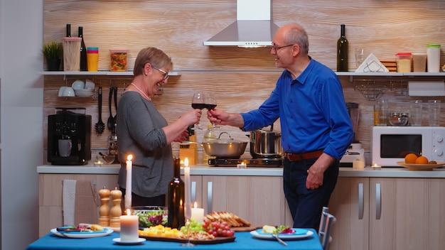 Vrolijke volwassen gepensioneerden grijsharige aantrekkelijke vrouw en man zitten in de buurt van de eettafel thuis in de keuken. ouder paar verliefd praten met een aangenaam gesprek tijdens een gezonde maaltijd.