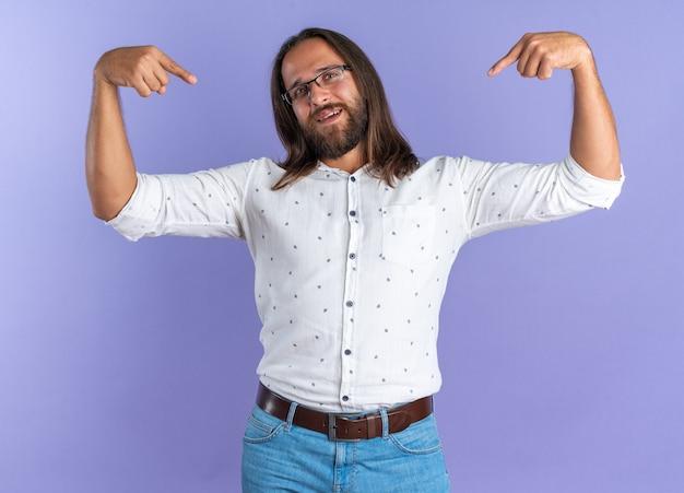 Vrolijke volwassen knappe man met een bril die naar een camera kijkt die naar de ruimte voor hem wijst, geïsoleerd op een paarse muur
