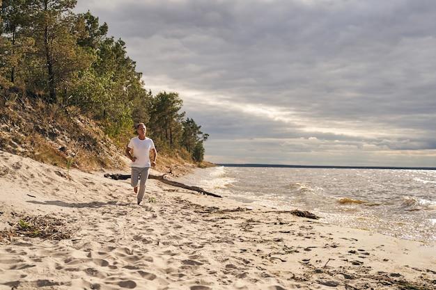 Vrolijke volwassen man begint de dag met cardiotraining tijdens het joggen in eenzaamheid langs de kust