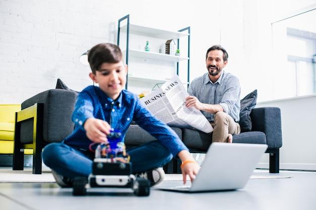 Vrolijke volwassen man die een krant leest terwijl zijn zoon robotapparaat test