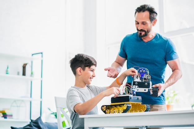 Vrolijke volwassen man die een robotapparaat vasthoudt terwijl hij zijn zoon helpt met een technisch project