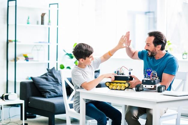 Vrolijke volwassen man die high five geeft aan zijn zoon terwijl hij tijd doorbrengt op een robotapparaat