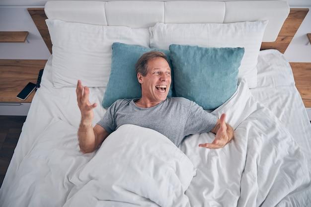 Vrolijke volwassen man die in zijn bed ligt en opzij kijkt naar het raam, blij dat hij vakantie heeft