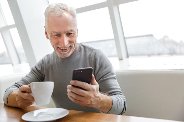 Vrolijke volwassen man die koffie drinkt en smartphone gebruikt terwijl hij binnenshuis in café zit