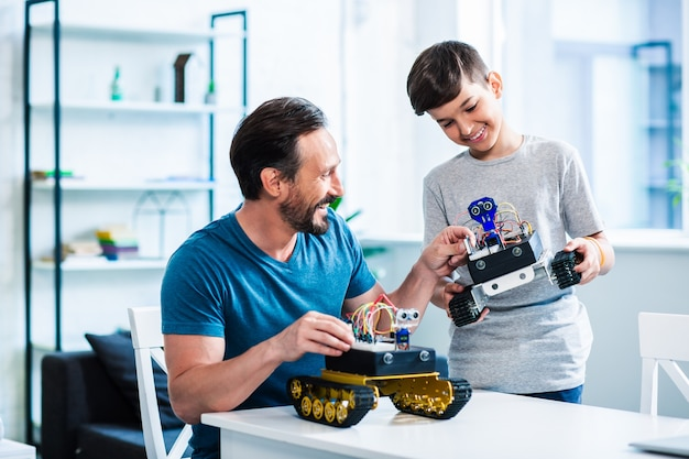 Vrolijke volwassen man die robotapparaat test terwijl hij geniet van zijn hobby met de zoon