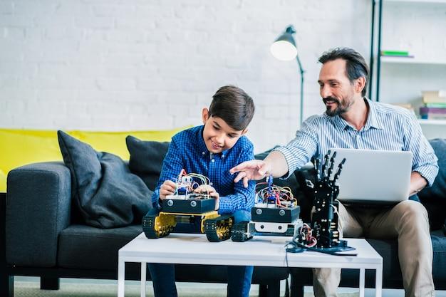Vrolijke volwassen man die zijn laptop gebruikt terwijl hij zijn zoon thuis helpt met robottechnologie