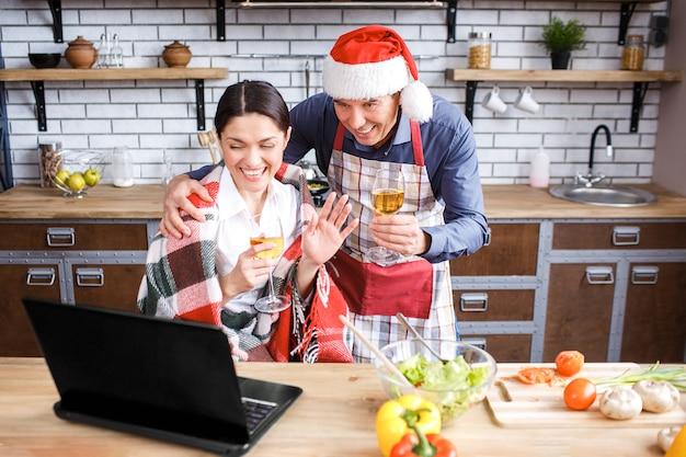 Vrolijke volwassen man en vrouw in keuken vieren nieuwjaar of kerstmis.