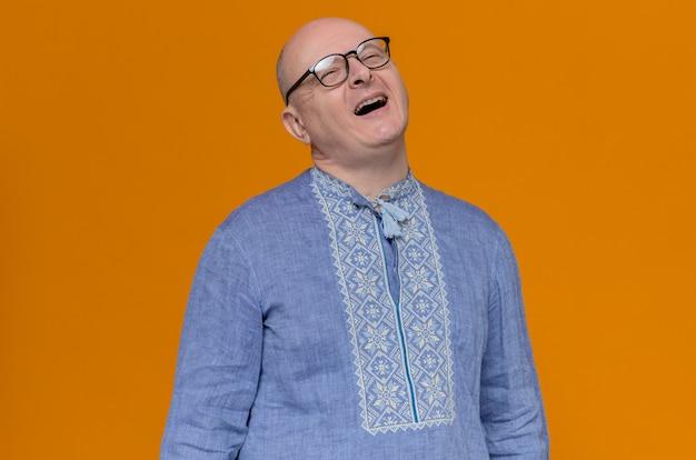 Vrolijke volwassen man in blauw shirt en met een bril die omhoog kijkt